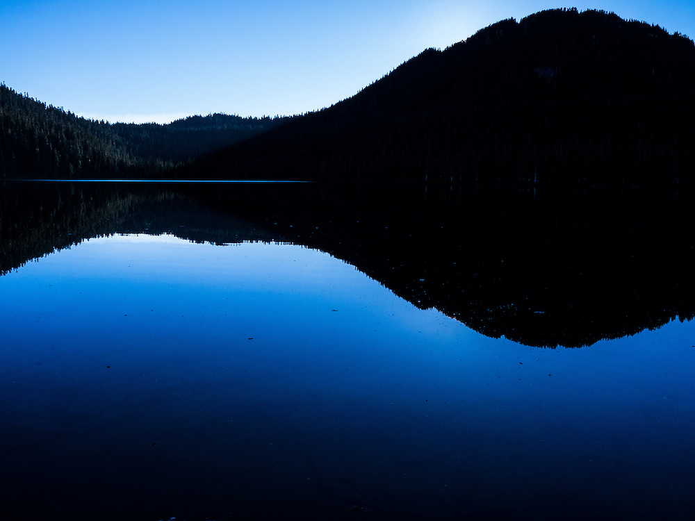 Clear blue sky is reflected in the deeper blue still water of Lake Helen McKenzie,in Strathcona Provincial Park, Vancouver Island BC Canada at dusk. A backlit rolling black treeline is silhouetted in the upper half of the image, with the blue of the sky above and the deeper blue hue of the lake below.