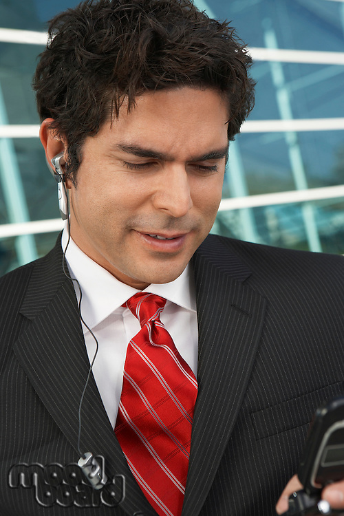 Businessman with earpiece, outdoors