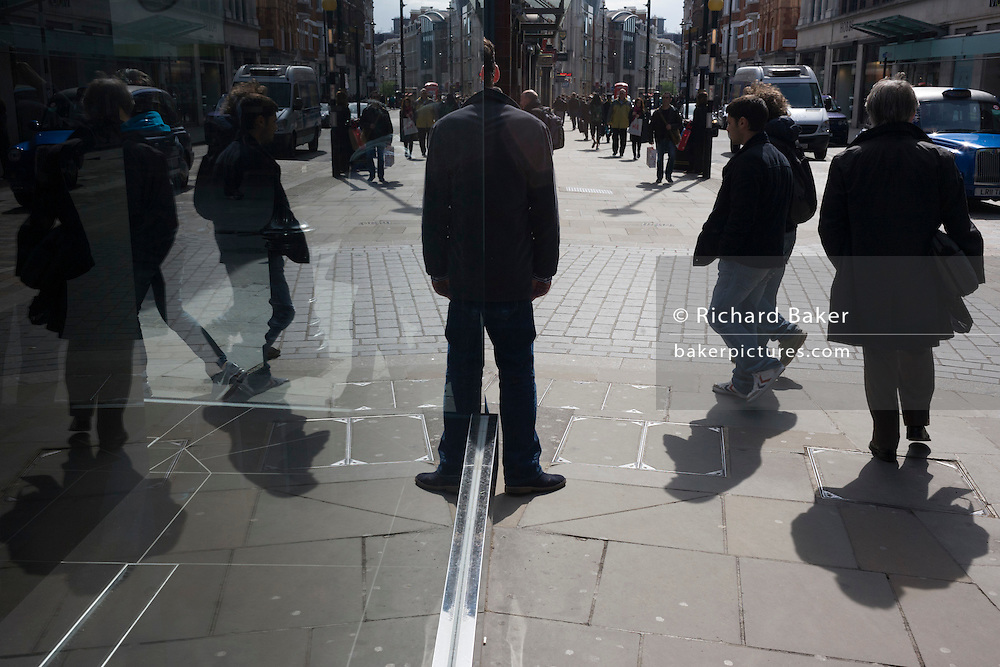 Seen through a polished sheet glass window, a man stands still to appear as a symmetrical image.