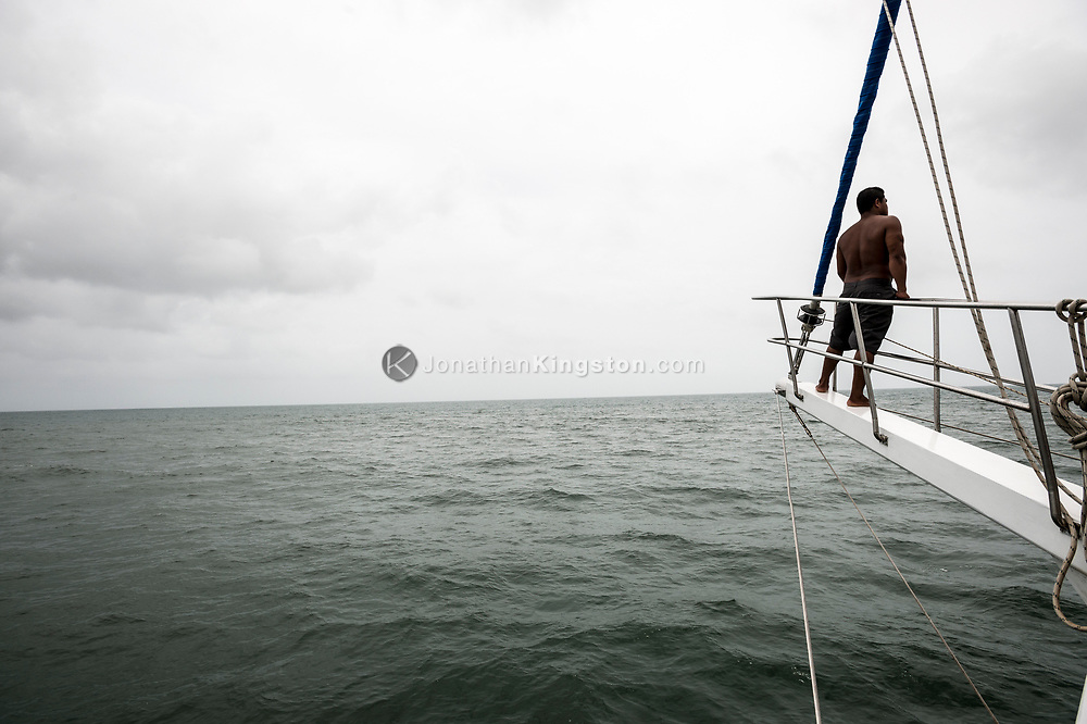A deck hand on the bow of a sailboat looking out to sea.