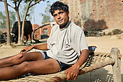 Rakesh, 25, from the village of Chandenamal, pop. 1500, Muzaffarnagar District, Uttar Pradesh, India, located along the banks of the severely polluted Krishni river, is sitting on a bed in front of his house, on Saturday, Apr. 29, 2008. Rakesh has been diagnosed a neurological disorder since one and a half years; it has left his legs and left hand almost paralysed while his cognitive skills have been severely affected. He can now walk only with the help of metal crutches and cannot carry on any sort of work or activity. Doctors believe his condition to be associated to the water contaminated with alarming levels of pesticides and heavy metals the family is drinking on an everyday basis.