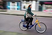 In Den Haag rijdt een vrouw op een OV-fiets.<br /> <br /> In The Hague a cyclist ride an OV-bike