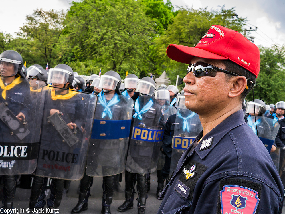 23 NOVEMBER 2012 - BANGKOK, THAILAND:  A Thai police supervisor watches officers prepare for expected mass protests in Bangkok Friday. Thai authorities have imposed the Internal Security Act (ISA), that enables police to call on the army if needed to keep order, and placed thousands of riot police in the streets around Government House in anticipation of a large anti-government protest Saturday. The group sponsoring the protest, Pitak Siam, said up to 500,000 people could turn out to protest against the government. They are protesting against corruption in the current government and the government's unwillingness to arrest or pursue fugitive former Prime Minister Thaksin Shinawatra, deposed in 2006 coup and later convicted on corruption charges. The current Thai Prime Minister is Yingluck Shinawatra, Thaksin's sister.      PHOTO BY JACK KURTZ