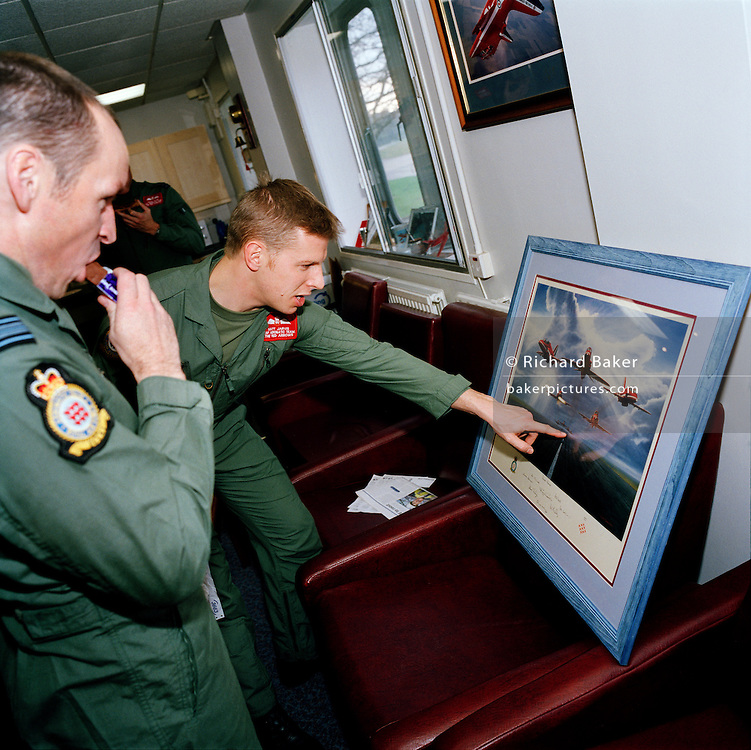 Pilots of the Red Arrows, Britain's RAF aerobatic team look at the details of romantic aviation posters in their crew room.