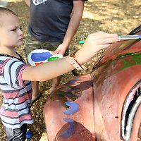 Gunner Bryson, 7, of Baldwyn, paints the Volkswagen Beetle while attending the 2019 Dudie Burger Festival Saturday morning at the Oren Dunn City Museum.