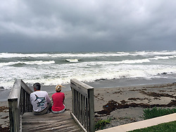 October 6, 2016 - Florida, U.S. - Dan Brendon and Helen Auchterlonie watch the surf on the south end of Jupiter Island Wednesday night at 6 pm as Hurricane Matthew approaches. Brendon lives across the street and had no plans to evacuate. (Credit Image: © Melanie Bell/The Palm Beach Post via ZUMA Wire)