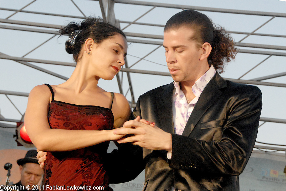 Tango Instructors Lucas Molina Gazcón and Cecilia Piccinni (right) dance on stage with Milongatron at the Santa Monica Pier during the 27th annual Twilight Dance Series on Thursday, August 25, 2011.