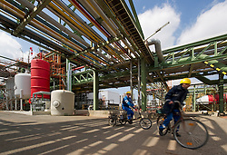 Employees use bicycles for transportation at the Solvay SA chemical plant in Antwerp, Belgium, on Thursday, April 22, 2010. Chlorine is the main product produced at Solvay's Antwerp facility.  Solvay SA is the world's largest supplier of Soda Ash or Sodium Carbonate and is also a major producer of caustic soda, hydrogen peroxide, chlorine and fluorinated products. (Photo © Jock Fistick)
