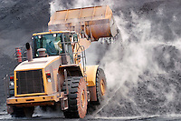 Front loader dumping mineral material on heap
