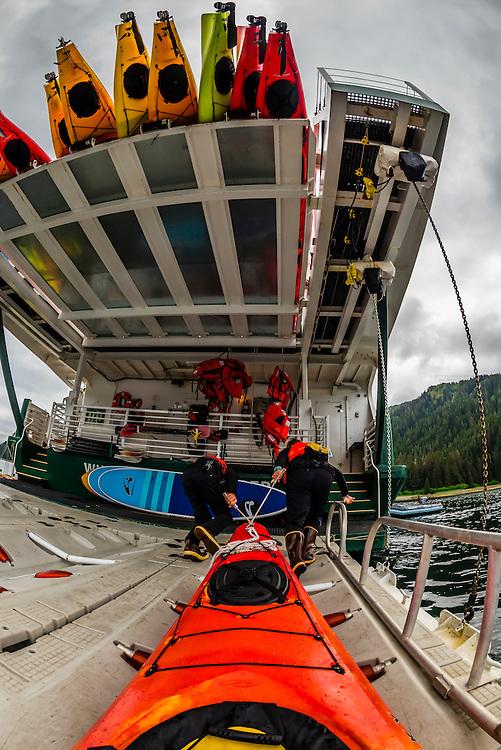Loading kayaks back aboard the Wilderness Explorer, Paterson Bay, Chichagof Island, Inside Passage, Southeast Alaska USA.