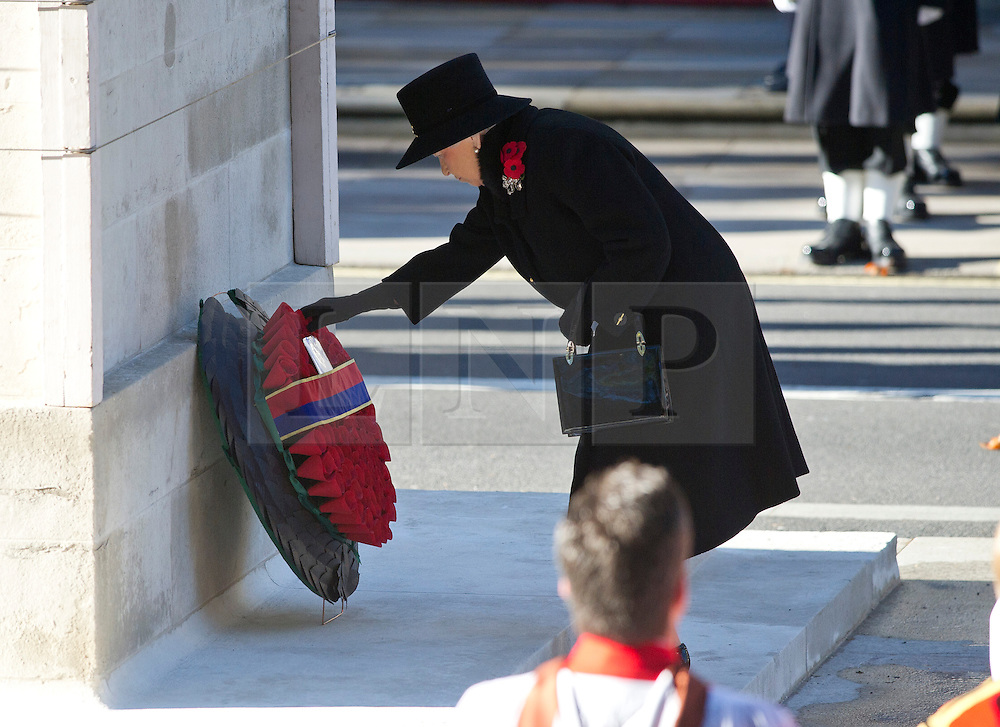 © London News Pictures. 10/11/2013. London, UK. HRH Queen Elizabeth II  laying a wreath during the Remembrance Day Ceremony at the Cenotaph war memorial in London, United Kingdom, on November 10, 2013 . Royalty and Politicians joined the rest of the county in honouring the war dead by gathering at the iconic memorial to lay wreaths and observe two minutes silence. Photo Credit: Ben Cawthra/LNP