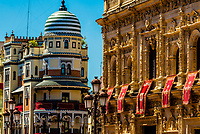 The Adriatic Building (Edificio de la Adriatica) on Avenue de la Constitucion on left and the Ayuntamiento (City Hall) on right, decorated for Holy Week (Semana Santa). Seville, Andalusia, Spain.
