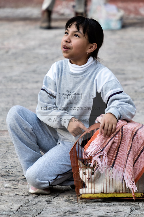 A young Mexican girl plays with her pet cat as she waits for the annual blessing of the animals on the feast day of San Antonio Abad at Oratorio de San Felipe Neri church in the historic center of San Miguel de Allende, Guanajuato, Mexico.
