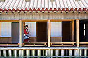 A staffer wearing traditional attire walks along the corridor outside the Sasunoma, which is located inside the grounds of Shuri Castle in Naha, Okinawa Prefecture, Japan, on June 24, 2012. The Sasonuma once functioned as an anteroom for the Royal princes but today forms part of the tea room facilities serving jasmine tea and traditional Ryukyu confectionary. Photographer: Robert Gilhooly
