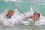 FIU spring breaker Miguel Irias, 22, holds a selfie stick as he videos his friends in the surf, Valerie Rincon, 22, left and Jennifer Perez, 22, at right, on South Beach.
