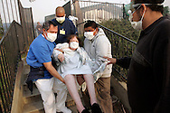 Oct 13, 2008 - Los Angeles, California, USA - Workers and volunteers evacuate an elderly patient from the Lifehouse Maclay Healthcare Center as an out of control wind whipped wildfire approaches on Monday October 13, 2008 in the San Fernando Valley