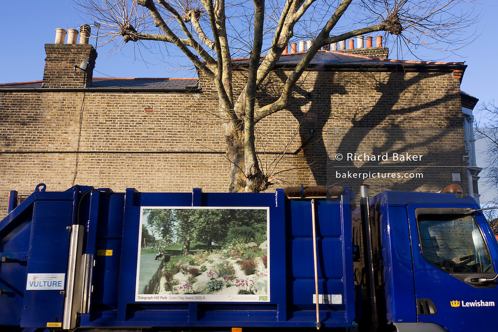 The shadow of bare branches on house wall belonging to an immense London Plane tree in the borough of Lewisham.