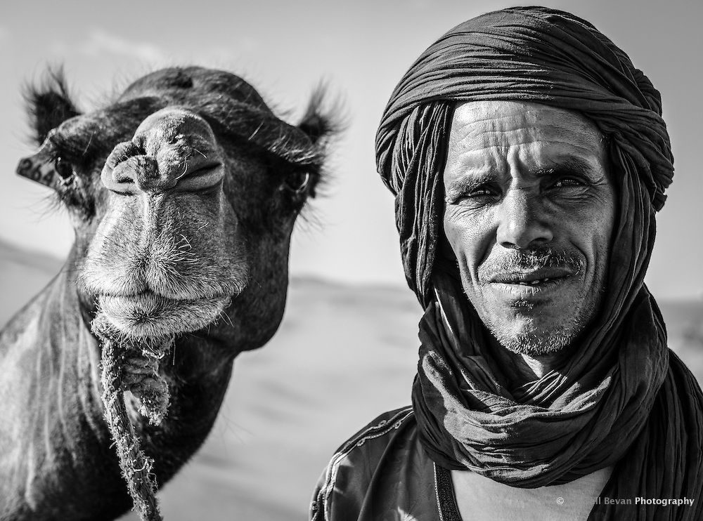A berber camel man poses for a portrait with his camel in Merzouga, Morocco