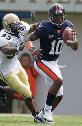 Virginia quarterback Jameel Sewell (10) scrambles past Georgia Tech defensive end Michael Johnson (93).  The Virginia Cavaliers football team faced the Georgia Tech Yellow Jackets at Scott Stadium in Charlottesville, VA on September 22, 2007.