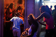 A young mother is feeding her baby, while another woman is taking care of her braids on the streets of Guadalupe, a small town near the city of Sao Tome, on the island of Sao Tome, Sao Tome and Principe, (STP) a former Portuguese colony in the Gulf of Guinea, West Africa.