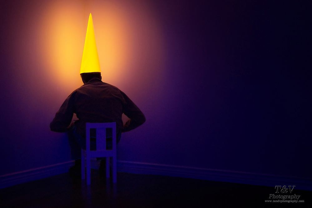 Man sitting in a corner with a glowing dunce cap on his head.Black light