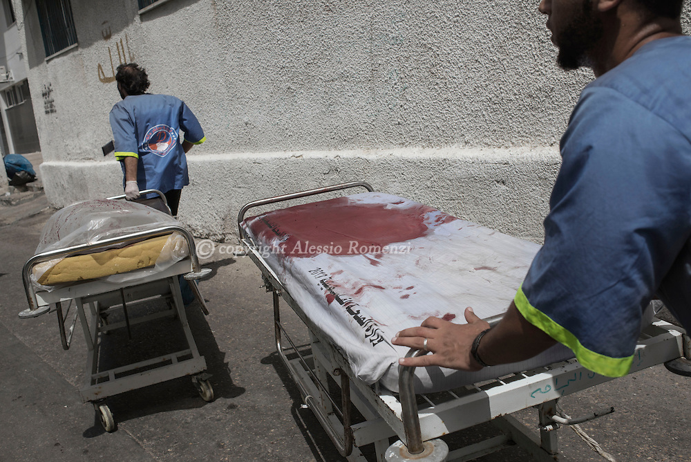 Gaza Strip, Gaza City: Male nurses push stretches blod stained in Al Shifa hospital in Gaza City on July 12, 2014. ALESSIO ROMENZI
