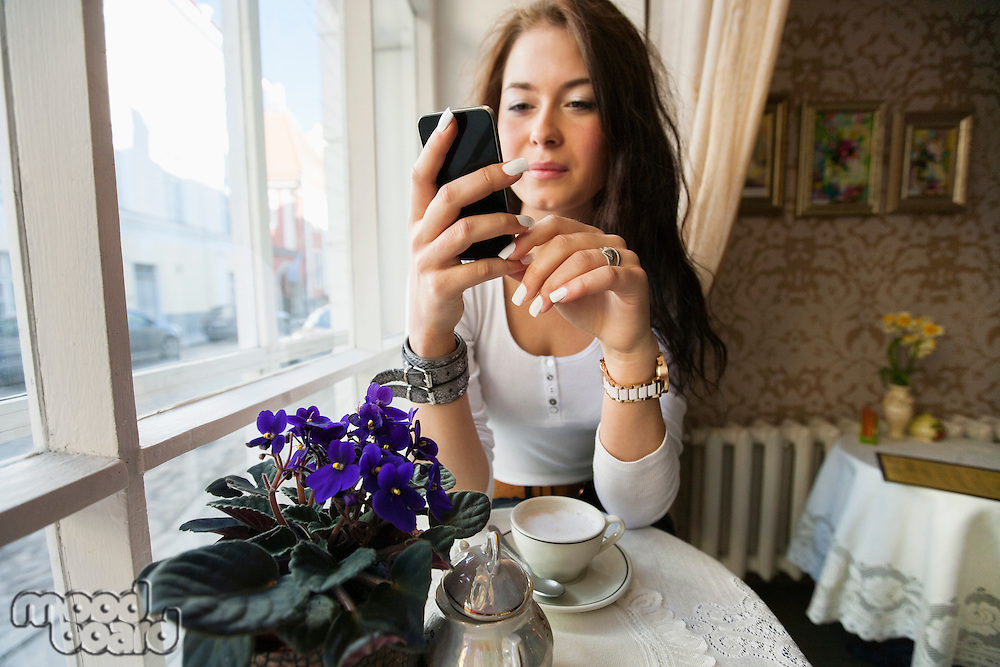 Young woman using smart phone at cafe table