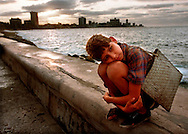 A street kid tries to keep himself warm in the evening breeze on the Malecon as the sun sets over Havana, Cuba.