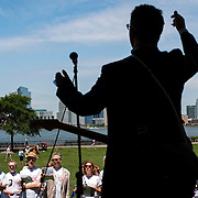 """June 21, 2014 - New York, NY : <br /> The city was flooded with music on Saturday as Make Music New York brought more than 1,300 free concerts to the city's streets and parks. The annual festival's program included """"And Death Shall Have No Dominion,"""" a piece by composer Pete M. Wyer, honoring the centenary of the birth of the poet Dylan Thomas. The piece -- a participatory singing event -- was performed by a synchronized headphone choir. The choir's singers began in smaller groups around lower Manhattan and culminated in a meeting in Battery Park City. Pete M. Wyer, foreground, leads the assembled musicians in the full piece after they have congregated in Nelson A. Rockefeller Park. CREDIT: Karsten Moran for The New York Times"""