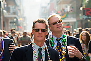 Two men are among the Mardi Gras crowd walking on Bourbon Street during the weekend before Fat Tuesday in New Orleans, LA