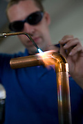 Heating system engineer, blow torching a copper pipe with soldier, at Kensa Engineering, Cornwall.