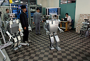 "The H7 robot walks without a safety harness at the Inoue-Inaba Robotics Lab. A joystick operating student, seated at right maneuvers the robot. Research Associate Satoshi Kagami (wearing a suit in the photo) walks with the robot, armed with its ""kill switch"" in case the robot malfunctions. Its predecessor, H6 hangs at left, near another student who is ready to step in, in the event that the robot falls. The researchers are fairly relaxed during the demonstration compared to those in other labs. University of Tokyo, Japan."