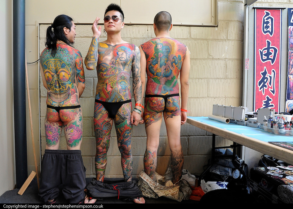 © Licensed to London News Pictures. 23/09/2011. LONDON, UK. Members of the 'Zi You Tattoo' stall show off their tattoos. The 7th London Tattoo convention takes place today (23 Sept 2011) at the Tobacco Dock in the East End of London. The convention attracts artists and customers from all over the world. It runs until 25th September 2011. Photo credit:  Stephen Simpson/LNP