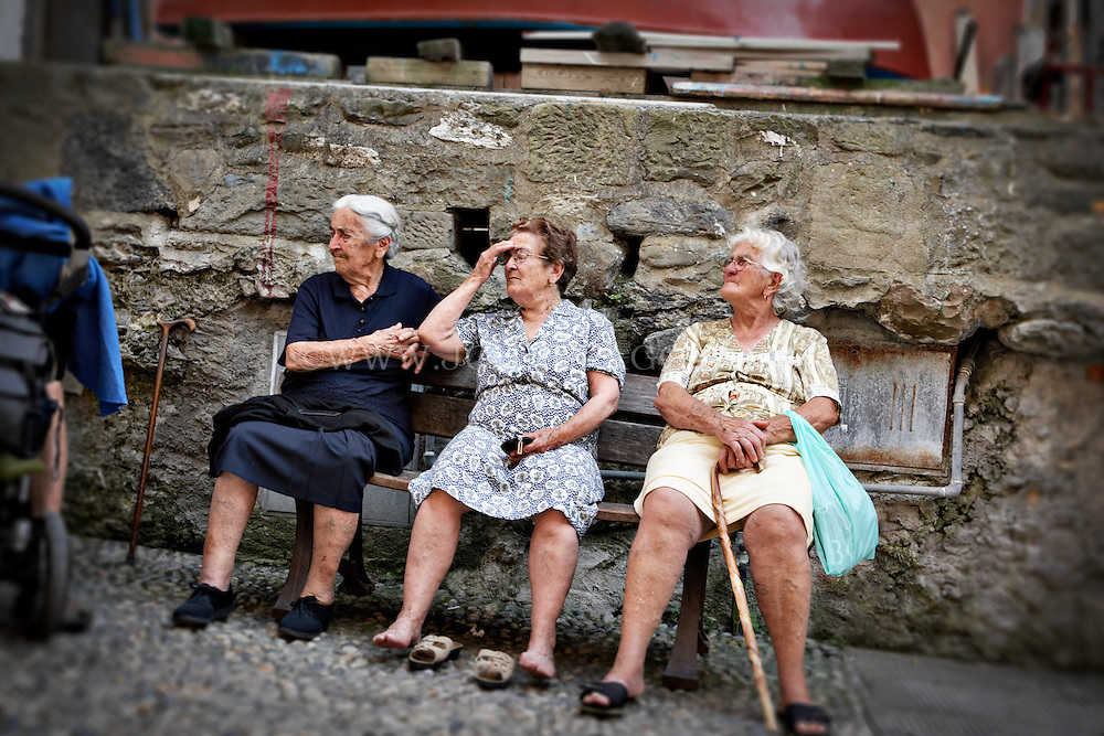 Photo Of Three Elderly Women Sitting On A Bench In