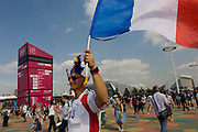 A French sports fan holds up his national flag in the air as he walks towards a venue in the Olympic Park during the London 2012 Olympics. Along with the Dutch and many Baltic countries, the French made their way across the Channel (La Manche) in great numbers to see their sports heroes perform in the various locations around London.