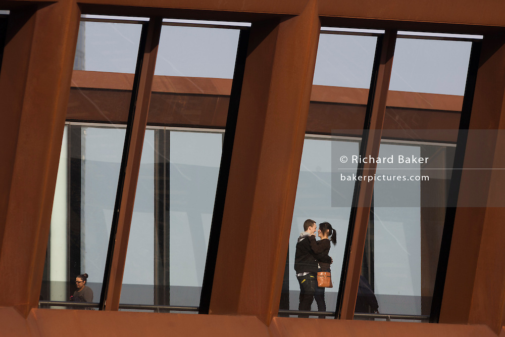 An embracing couple on the bridge that connects Stratford's mainline station and the Westfield shopping mall near the 2012 Olympic Park.