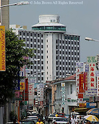 The City Bayview Hotel towers over a busy shopping district with many signs in Penang, Malaysia.