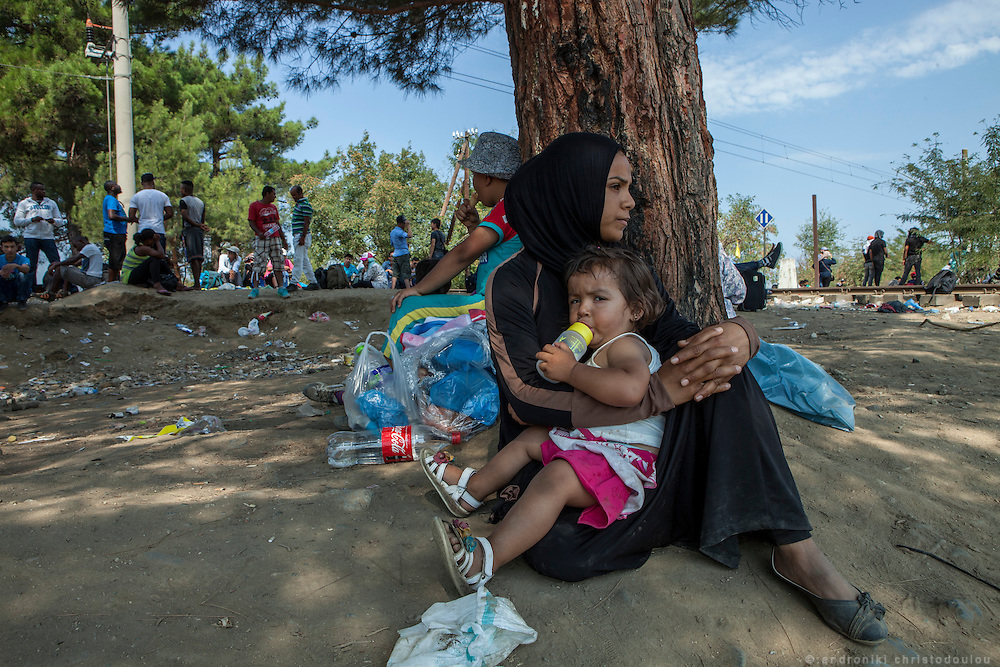 Refugee mother with her child waiting for her turn to cross the border.<br /> Refugees arrive at Eidomeni border by bus and some times on foot. There they can cross to the republic of Macedonia on foot.