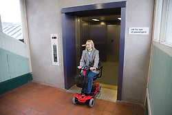 Woman driving electric mobility scooter exiting a lift at a railway station,