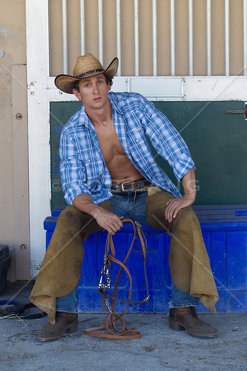 cowboy with an open shirt sitting down holding a horse bridle