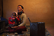 A family in their warm kitchen, also used as a living room in the cold months of Spiti, Himachal Pradesh, India
