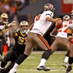January 2, 2011; New Orleans, LA, USA; Tampa Bay Buccaneers quarterback Josh Freeman (5) stiff arms and escapes from New Orleans Saints defensive end Will Smith (91) during the third quarter at the Louisiana Superdome. Mandatory Credit: Derick E. Hingle