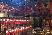 Worshippers inside the Man Mo Temple with giant hanging incense coils is a tribute to the God of Literature and the God of War and was built in 1847 in Sheung Wan District of Hong Kong Island. The Taoist temple is the largest Man Mo Temple in Hong Kong and includes two additional temples for Buddhist and Taoist deities.