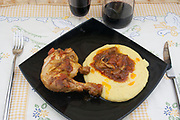 chicken cacciatore with polenta side view from above close-up on balck dish and rustic tablecloth background,italian food
