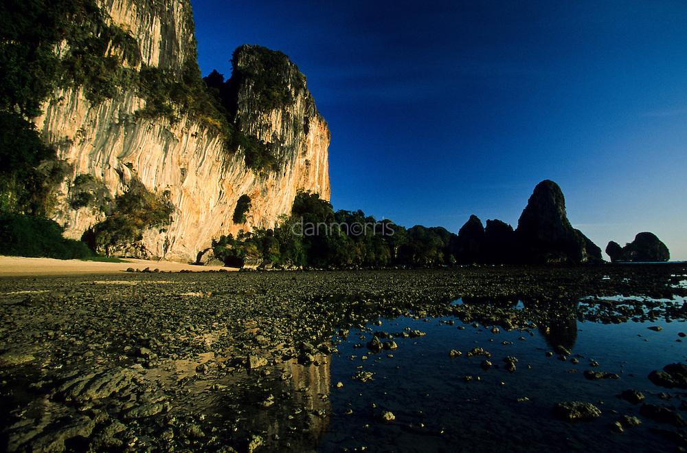 Yellow Karst Cliffs glow in evening light at low tide, Tonsai Beach, Thailand