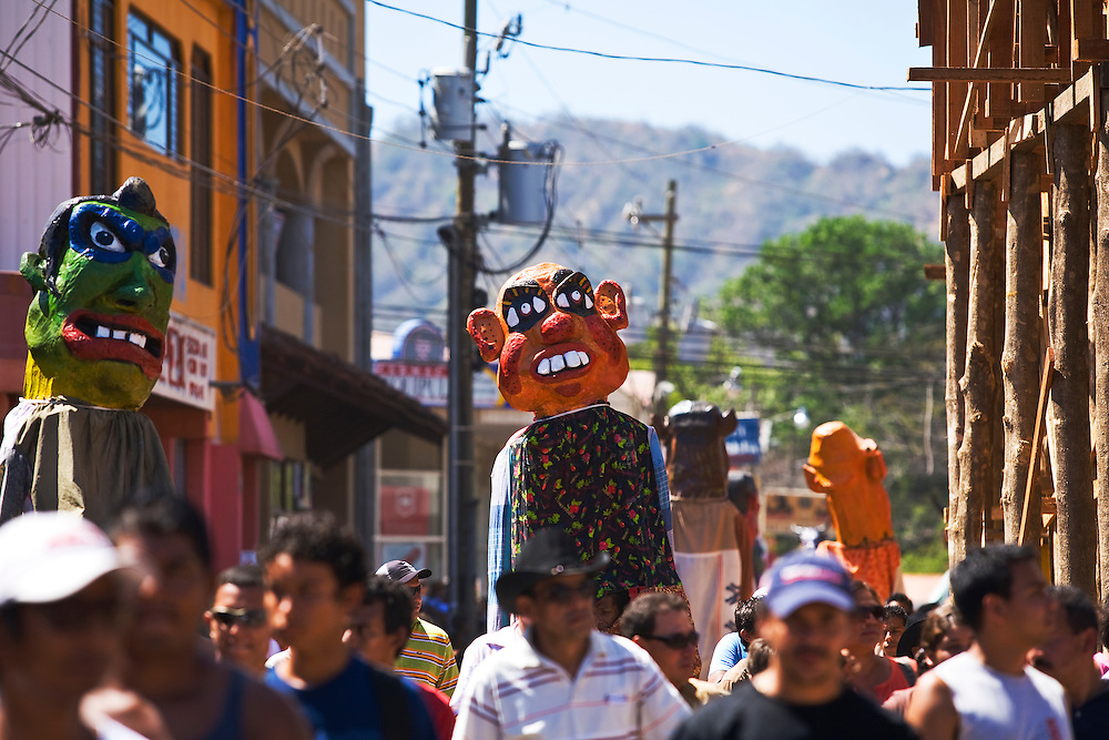 These are Mascaradas walking among the crowd, they are a feature of every important Costa Rican festivity. During the annual festivities in San Cruz, people dress in these effigies and dance in a crazed manner in the streets.