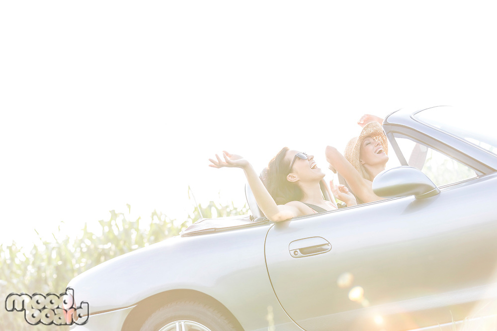 Cheerful female friends enjoying road trip in convertible on sunny day