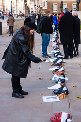 London, December 10th 2014. The shoes of hundreds of victims who died in Ireland, North and South during the Troubles are lined up opposite Downing Street as families demand that a proper investigation into over 3,600 deaths and 40,000 injuries on all sides, sets the truth free. PICTURED: A woman takes pictures of the shoes lined upo on Richmond Terrace.
