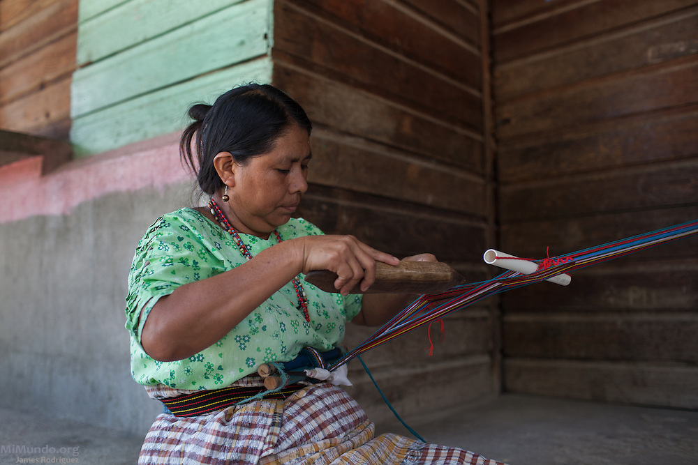 Maria Uscap Iboy, 43, weaves at home in the community of Pacux, where the former Achi Mayan residents of Rio Negro were resettled after the destruction of their village, numerous massacres, and flooding of the Chixoy river basin. Uscap Iboy survived the March 13, 1982, massacre at Pak'oxom along with her brother Juan as they, along with 16 other children, were taken as child slaves by civil patrolmen from Xococ. She remained in custody for two years before she reunited with community members from Rio Negro. Pacux, originally planned as a so-called model village where they army would resettle civilians from areas controlled by the guerrillas, lies in the outskirts of Rabinal city. It is plagued today by poverty and crime as the citizens of Pacux are still outcast as former guerrillas by large sectors in Rabinal. Pacux, Rabinal, Baja Verapaz, Guatemala. July 16, 2014.