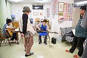 Efter den gemensamma lördagsmiddagen rockar de boende på New Start loss på gitarrerna, på New Starts center i östra Tokyo.